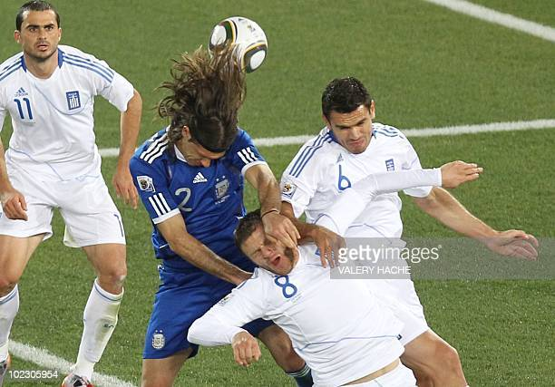 Argentina's defender Martin Demichelis heads the ball past Greece's defender Avraam Papadopoulos and Greece's midfielder Alexandros Tziolis during...