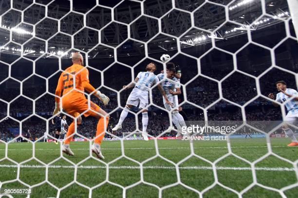 Argentina's defender Nicolas Otamendi and Argentina's midfielder Lucas Biglia head the ball past Argentina's goalkeeper Willy Caballero during the...