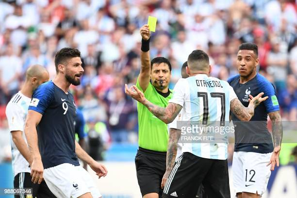 Argentina's defender Nicolas Otamendi is shown a yellow card by Irani referee Alireza Faghani during the Russia 2018 World Cup round of 16 football...