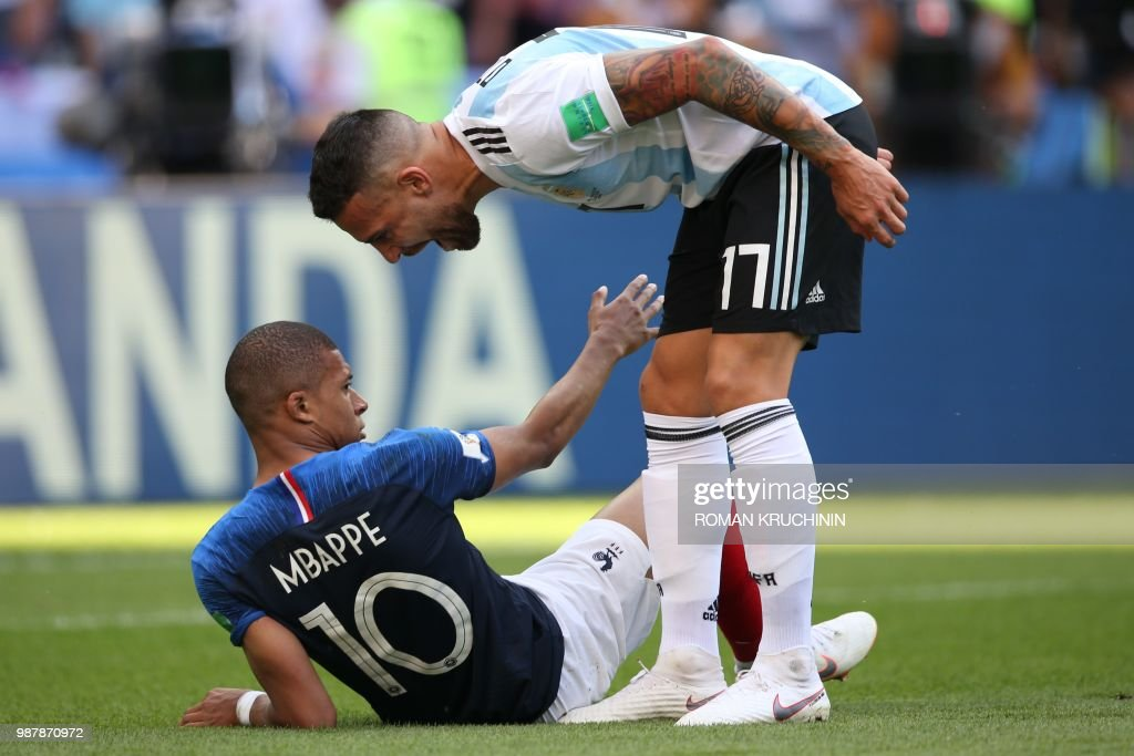 TOPSHOT - Argentina's defender Nicolas Otamendi leans over France's forward Kylian Mbappe (L) after he was fouled during the Russia 2018 World Cup round of 16 football match between France and Argentina at the Kazan Arena in Kazan on June 30, 2018. (Photo by Roman Kruchinin / AFP) / RESTRICTED