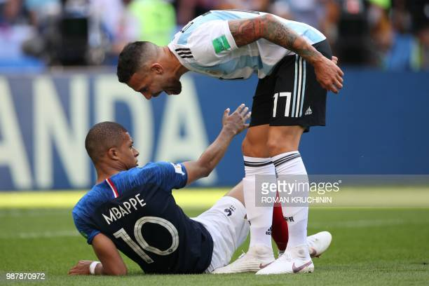 TOPSHOT Argentina's defender Nicolas Otamendi leans over France's forward Kylian Mbappe after he was fouled during the Russia 2018 World Cup round of...