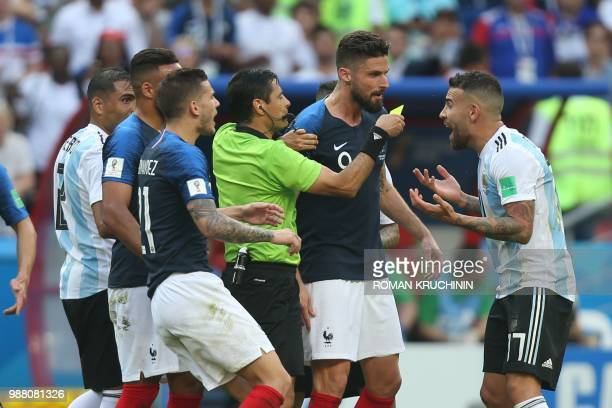 Argentina's defender Nicolas Otamendi receives a yellow card from Iranian referee Alireza Faghani as France's and Argentina's players scuffle during...
