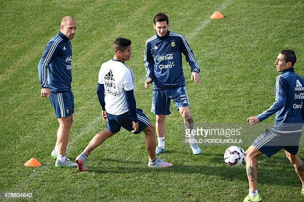 Argentina's defenders Pablo Zabaleta and Marcos Rojo vie for the ball with forwards Lionel Messi and Angel Di Maria during a training session at the...