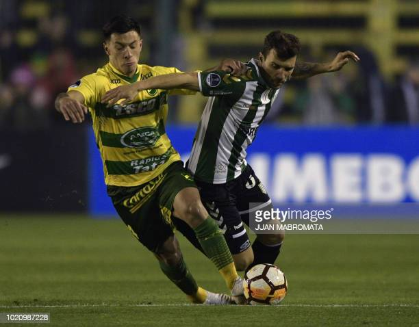 Argentina's Defensa y Justicia defender Lisandro Martinez vies for the ball with Argentina's Banfield midfielder Nicolas Bertolo during their Copa...