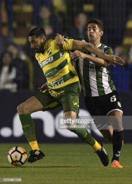 Argentina's Defensa y Justicia midfielder Jonas Gutierrez vies for the ball with Argentina's Banfield midfielder Emanuel Cecchini during their Copa...