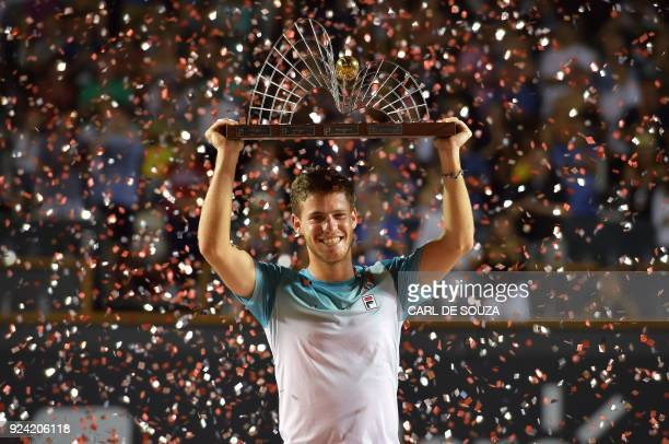 TOPSHOT Argentina's Diego Schwartzman celebrates with the trophy after beating Spain's Fernando Verdasco during their ATP World Tour Rio Open singles...