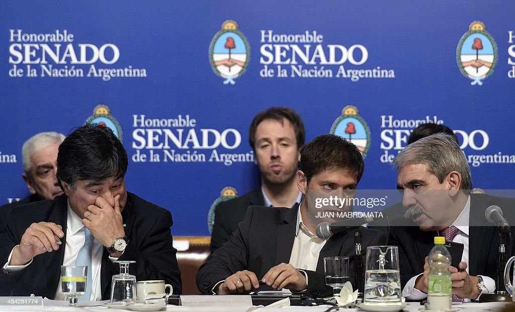 Argentina's Economy Minister Axel Kicillof (C) talks to Senator Anibal Fernandez (R) during their appearance in the Congress about the bill to pay the debt at the Banco Nacion, Buenos Aires on August 27, 2014.