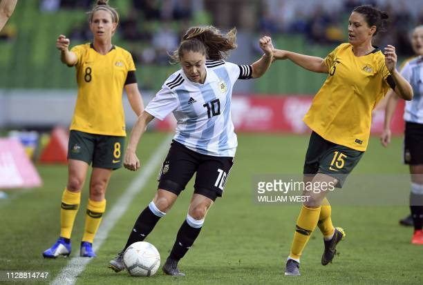 Argentina's Estefania Banini evades Australia's Emily Gielnik and Elise KellondKnight during their Women's Cup of Nations football match in Melbourne...