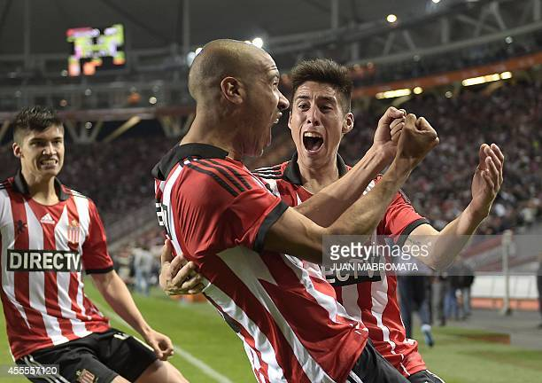 Argentina's Estudiantes forward Diego Vera celebrates with teammates defender Pablo Rosales and midfielder Joaquin Correa after scoring against...