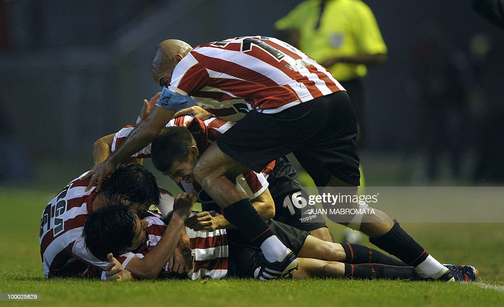Argentina's Estudiantes midfielder Enzo Perez (C-bottom) celebrates with teammates midfielder Matias Sanchez (L), defender German Re and midfielder Juan Veron after scoring team's second goal against Brazil's Internacional during the second leg of the Copa Libertadores 2010 quarterfinals football match at Centenario stadium in Quilmes, south Buenos Aires, on May 20, 2010. AFP PHOTO / Juan Mabromata