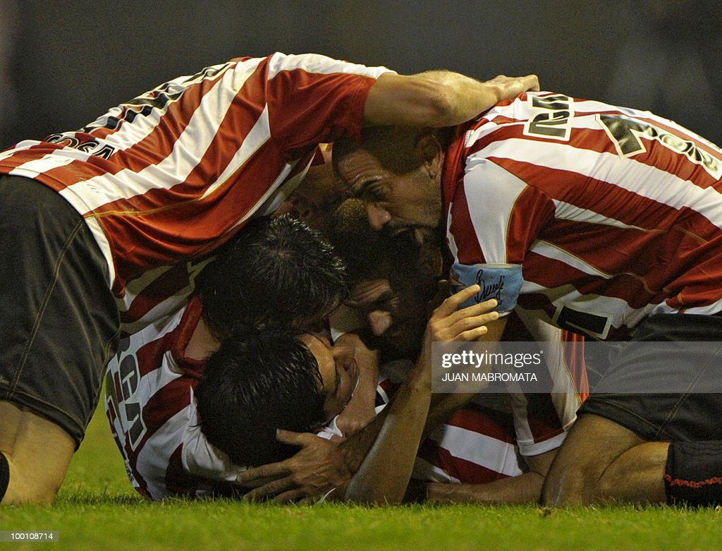 Argentina's Estudiantes midfielder Enzo Perez (C-bottom) celebrates with teammates midfielder Matias Sanchez (2-L), defender German Re, midfielder Juan Veron (R) and midfielder Jose Sosa (L) after scoring their team's second goal against Brazil's Internacional during the second leg of the Copa Libertadores 2010 quarterfinals football match at Centenario stadium in Quilmes, south Buenos Aires, on May 20, 2010. AFP PHOTO / Juan Mabromata