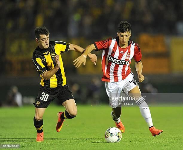 Argentina's Estudiantes player Joaquin Correa is marked by Uruguay's Penarol player Alejandro Silva during their Copa Sudamericana football match at...