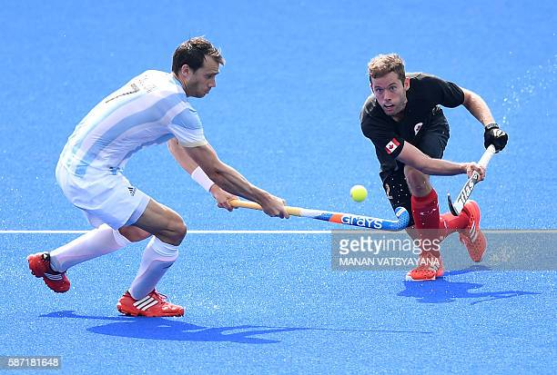 Argentina's Facundo Callioni vies for the ball with Canada's Benjamin Martin during the men's field hockey Canada vs Argentina match of the Rio 2016...