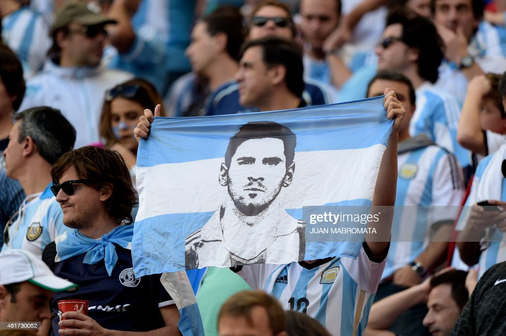 Argentina's fans hold a flag with a picture of Argentina's forward and captain Lionel Messi during a quarter-final football match between Argentina and Belgium at the Mane Garrincha National Stadium in Brasilia during the 2014 FIFA World Cup on July 5, 2014. AFP PHOTO / JUAN MABROMATA