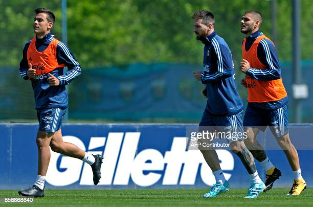 Argentina's farwards Lionel Messi Paulo Dybala and Mauro Icardi run during a training session in Ezeiza Buenos Aires on October 7 2017 ahead of a...