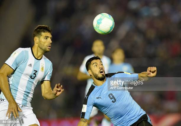 Argentina's Federico Fazio and Uruguay's Luis Suarez eye the ball during their 2018 World Cup qualifier football match in Montevideo on August 31...