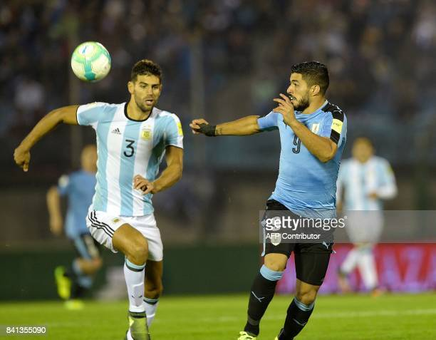 Argentina's Federico Fazio and Uruguay's Luis Suarez run for the ball during their 2018 World Cup qualifier football match in Montevideo on August 31...