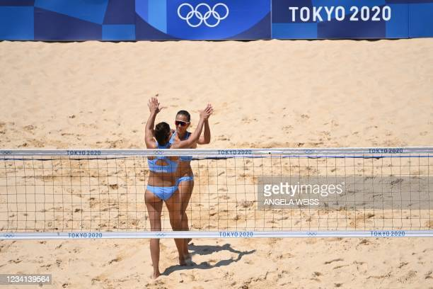 Argentina's Fernanda Pereyra celebrates after scoring with Argentina's Ana Gallay in their women's preliminary beach volleyball pool C match between...