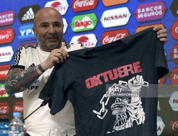 Argentina's football team coach Jorge Sampaoli displays a jersey with the name of the album Oktubre by Argentine rock group 'Los redonditos de...