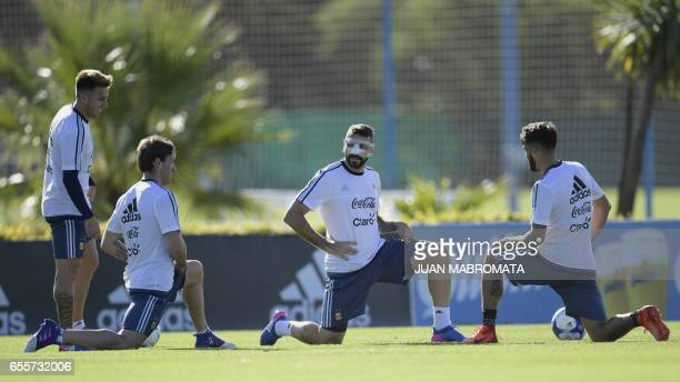 Argentina's footballers Julio Buffarini Lucas Biglia Lucas Pratto and Emmanuel Mas stretch during a training session of the national football team in...