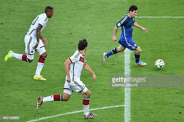 Argentina's forward and captain Lionel Messi runs to shoot past Germany's defender Jerome Boateng during the 2014 FIFA World Cup final football match...