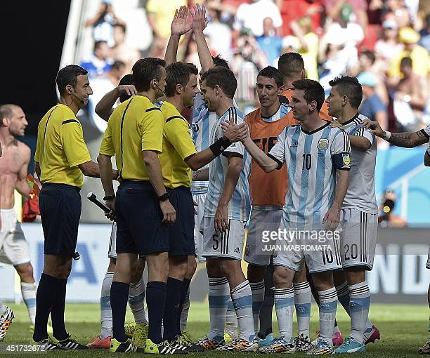 Argentina's forward and captain Lionel Messi shakes hands with referees after winning the quarterfinal football match between Argentina and Belgium...