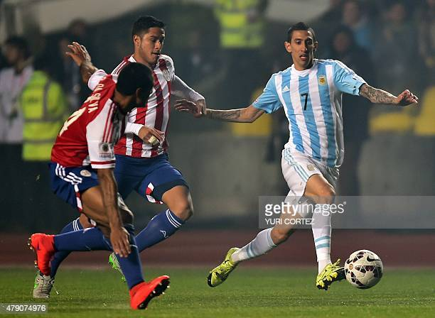 Argentina's forward Angel Di Maria is marked by Paraguay's defenders Marcos Caceres and Paulo Da Silva during their Copa America semifinal football...