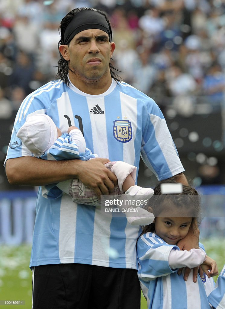 Argentina's forward Carlos Tevez poses with his daughters before a friendly football match against Canada at the Monumental stadium in Buenos Aires, on May 24, 2010. Argentina is flying to South Africa for the World Cup finals on Friday, and will play their first match against Nigeria on June 12 in Johannesburg. AFP PHOTO/Daniel GARCIA