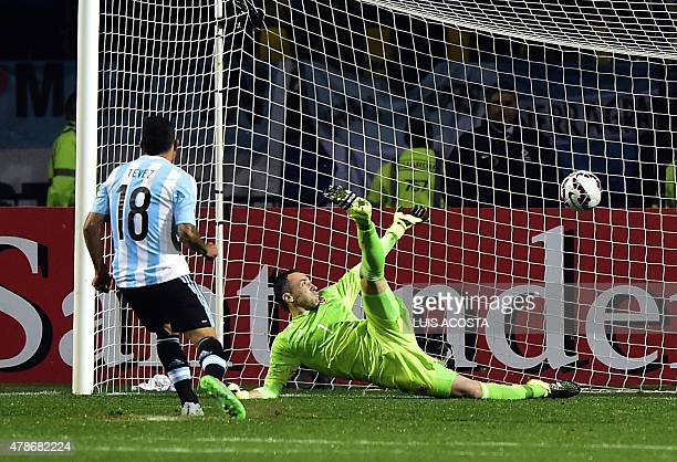Argentina's forward Carlos Tevez scores his penalty during the shootout against Colombia to defeat them 54 in their 2015 Copa America football...