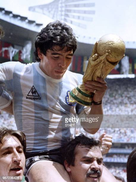 Argentina's forward Diego Maradona is carried on the shoulders of fans as he does a victory lap holding the FIFA World Cup after Argentina defeated...