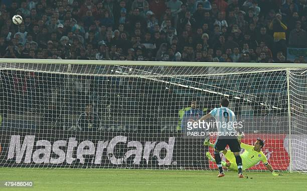 Argentina's forward Gonzalo Higuain kicks the ball over the goal as Chile's goalkeeper Claudio Bravo dives during the penalty shootout of the 2015...