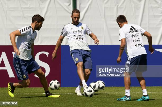 Argentina's forward Gonzalo Higuain passes the ball to midfielder Cristian Pavon next to defender Federico Fazio during a training session at the...