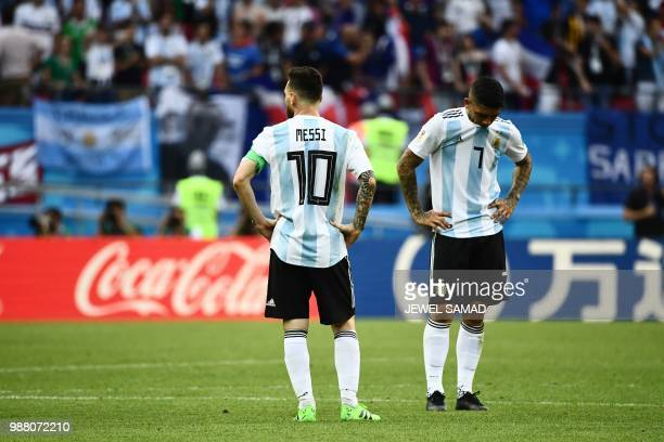 TOPSHOT Argentina's forward Lionel Messi and Argentina's midfielder Ever Banega react to their loss during the Russia 2018 World Cup round of 16...