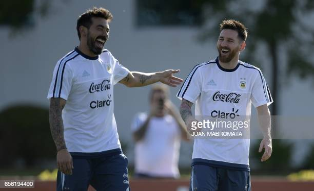 Argentina's forward Lionel Messi and midfielder Ezequiel Lavezzi laugh during a training session in Ezeiza Buenos Aires on March 21 2017 ahead of...