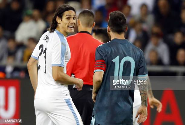 Argentina's forward Lionel Messi and Uruguay's forward Edinson Cavani are pictured on the pitch the friendly football match between Argentina and...