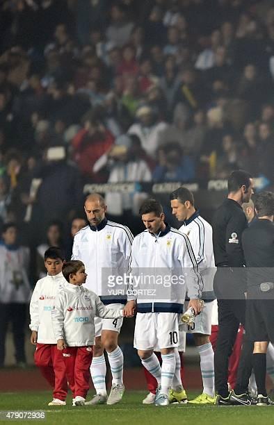 Argentina's forward Lionel Messi , Argentina's midfielder Javier Mascherano and Argentina's defender Martin Demichelis enter the field before their...