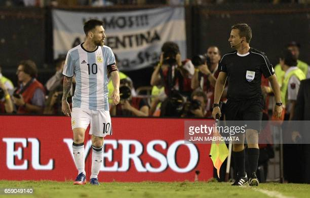 Argentina's forward Lionel Messi argues with first assistant referee Emerson Augusto de Carvalho during the half time of their 2018 FIFA World Cup...