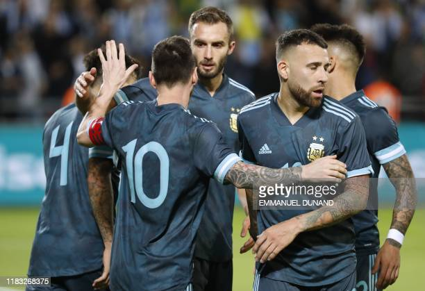 Argentina's forward Lionel Messi celebrates with team mates after scoring during the friendly football match between Argentina and Uruguay at the...