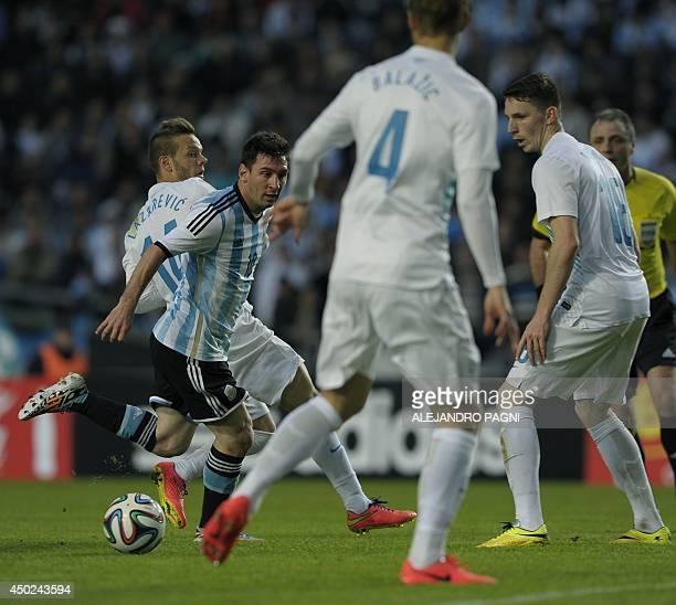Argentina's forward Lionel Messi controls the ball between Slovenia's defender Gregor Balazic midfielders Rajko Rotman and Dejan Lazarevic during a...