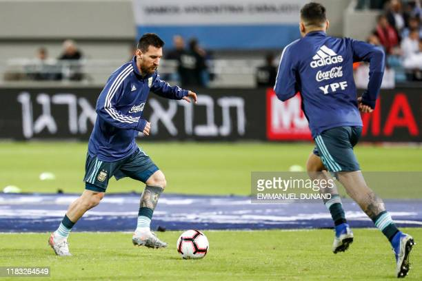 Argentina's forward Lionel Messi dribbles a ball while warming up ahead of the friendly football match between Argentina and Uruguay at the...