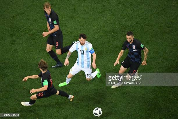 Argentina's forward Lionel Messi fights for the ball with Croatia's midfielder Luka Modric Croatia's defender Ivan Strinic and Croatia's midfielder...