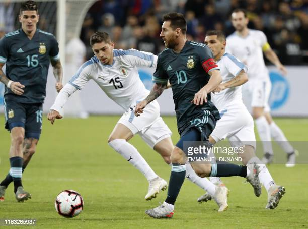 Argentina's forward Lionel Messi fights for the ball with Uruguay's midfielder Federico Valverde during the friendly football match between Argentina...