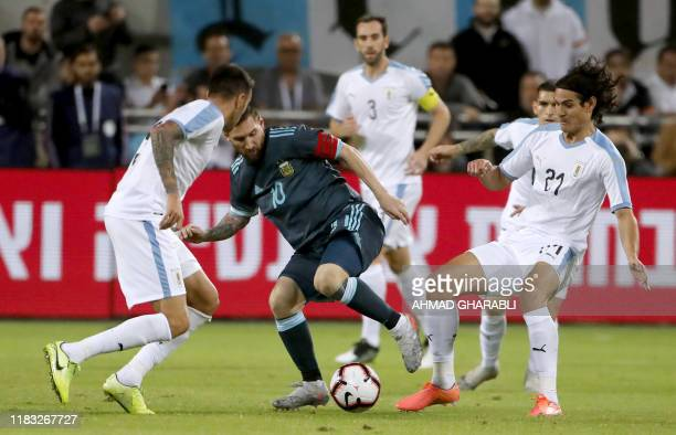 Argentina's forward Lionel Messi fights for the ball with Uruguay's forward Edinson Cavani during the friendly football match between Argentina and...
