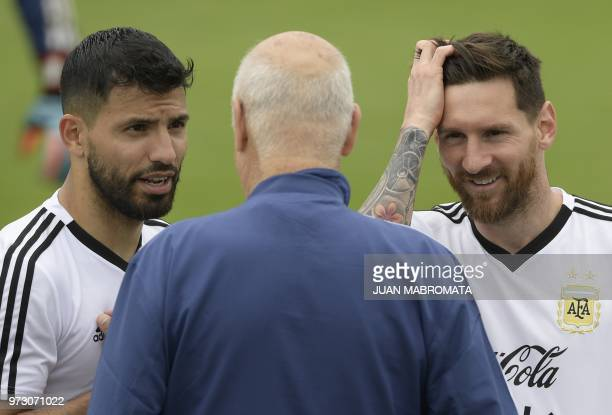 Argentina's forward Lionel Messi forward Sergio Aguero and Omar Souto manager of logistics of the Argentine football federation chat during a...