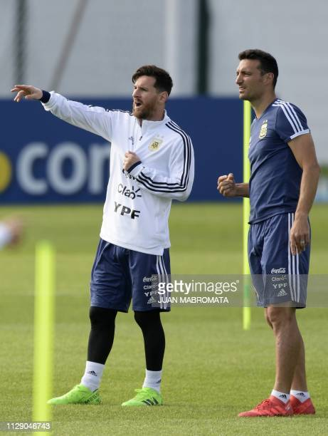 Argentina's forward Lionel Messi gestures next to assistant coach Lionel Scaloni during a training session at the team's base camp in Bronnitsy near...