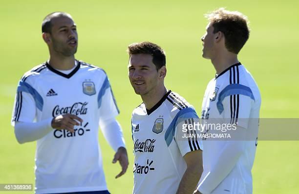 Argentina's forward Lionel Messi gestures next to midfielder Javier Mascherano and midfielder Lucas Biglia during a training session at 'Cidade do...