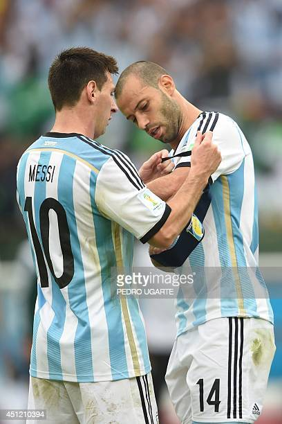 Argentina's forward Lionel Messi gives the captain armband to midfielder Javier Mascherano before leaving the field during a Group F football match...