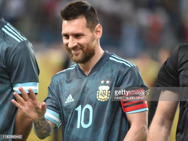 Argentina's forward Lionel Messi greets a fan following the friendly football match between Brazil and Argentina at the King Saud University stadium...