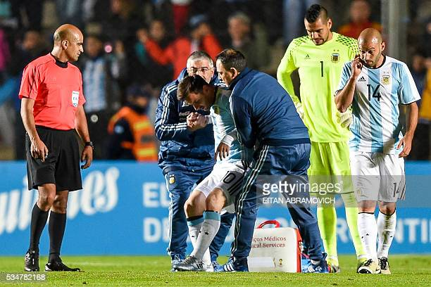 Argentina's forward Lionel Messi is assisted after being injured during a friendly football match against Honduras at Bicentenario stadium in San...
