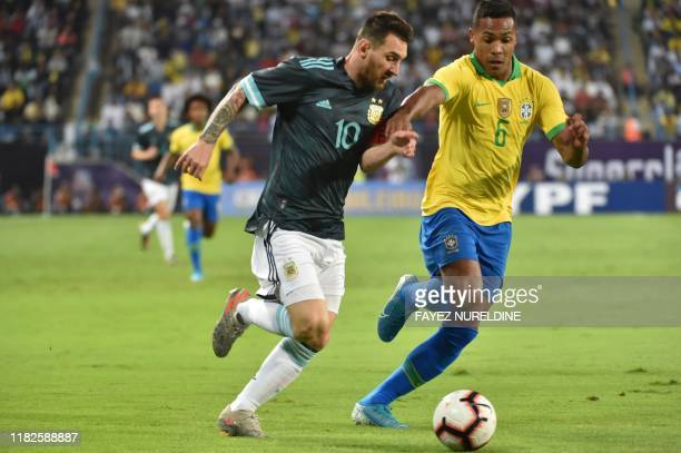 Argentina's forward Lionel Messi is marked by Brazil's defender Alex Sandro during the friendly football match between Brazil and Argentina at the...